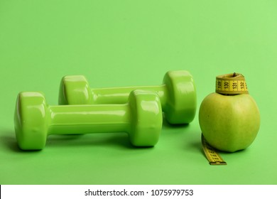 Dumbbells in bright green color, measure tape and fruit on green background. Sports and healthy regime symbols. Tape measure in yellow color by barbells and juicy apple. Diet and sport regime concept