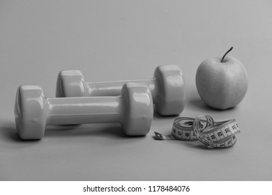 Dumbbells in bright green color, twisted measure tape and fruit on green background. Healthy regime symbols. Athletics and weight loss concept. Tape measure in cyan blue color near barbells and apple
