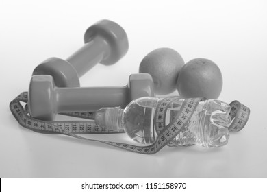 Dumbbells in bright green color, water bottle, measure tape and fruit on white background. Sports and healthy regime equipment. Barbells made of plastic by juicy oranges. Diet and sport regime concept