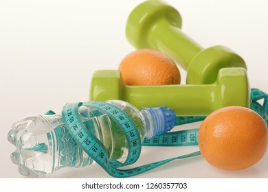 Dumbbells in bright green color, water bottle, measure tape and fruit on white background. Barbells made of plastic by juicy oranges. Diet and sport regime concept. Sports and healthy regime equipment