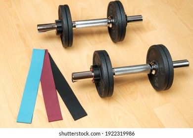 家の床にダンベルと弾力バンド。 ロックダウン中も体調を維持。 体力訓練用フィットネス機器