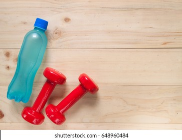 Dumbbells and electrolyte drink on wooden texture and background, fitness and exercise concept