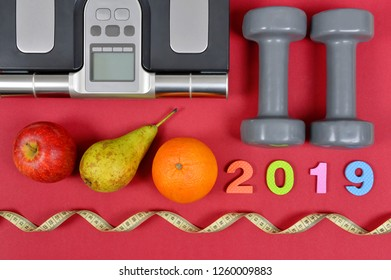 Dumbbells with fruits and body mass index scale on red background. Healthy resolutions for the New Year 2019.