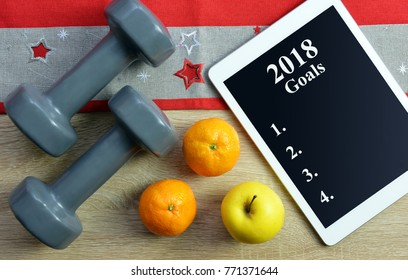 Dumbbells with fruits and tablet computer on wooden desk. Healthy resolutions for the New Year 2018.