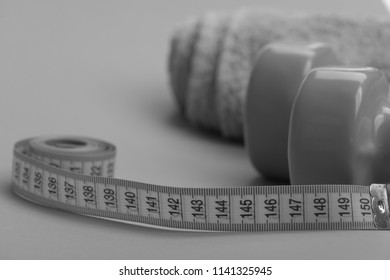 Dumbbells in green color, twisted measure tape and towel on green background. Diet and sport regime concept. Tape measure in yellow color near lightweight barbells, close up. Healthy regime equipment