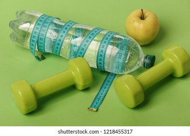 Dumbbells in green color, water bottle, measure tape and fruit on green background. Healthy lifestyle and food concept. Healthy regime equipment. Bottle tied with cyan ruler by barbells and apple