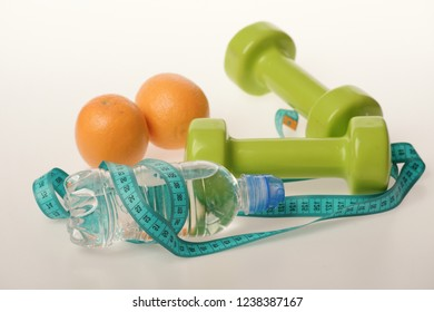 Dumbbells in green color, water bottle, measure tape and fruit on white background. Sports and healthy regime equipment. Barbells made of plastic near juicy oranges. Athletics and weight loss concept