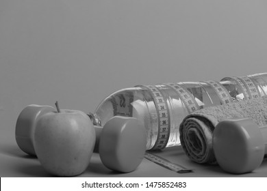 Dumbbells in green color, water bottle, measure tape, towel and fruit on green background. Barbells by juicy green apple, close up. Diet and sport regime concept. Healthy lifestyle symbols, copy space