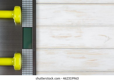 Dumbbells lying on the scales on white wood background. Concept plan.