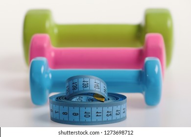 Dumbbells made of blue, pink and green plastic on white defocused background. Barbells in small size next to blue measure tape, close up. Fit shape and sport concept. Health regime and fitness symbols