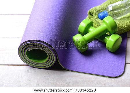 0b5949b66bec6 Dumbbells made of green plastic on light wooden background. Sports and healthy  lifestyle concept.