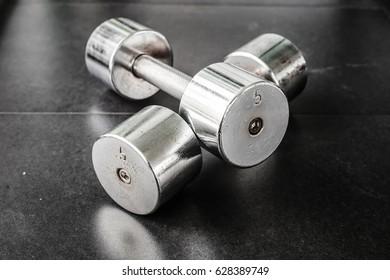 Dumbbells in modern sports club. Weight training equipment