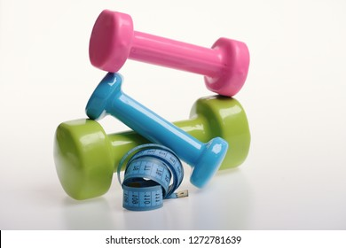 Dumbbells near blue rolled ruler on white background. Measure tape and pink, green and blue barbells on each other. Health regime and fitness symbols. Fit shape and sport concept