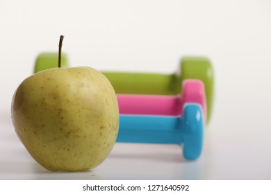 Dumbbells near green apple on white background. Healthy lifestyle and sports concept. Apple fruit and pink, blue and green barbells put in pattern. Health regime and fitness symbols, selective focus
