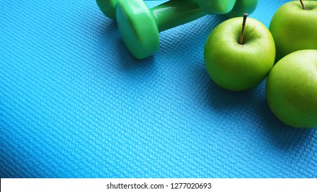 Dumbbells near green apples on blue background. Healthy lifestyle and sports concept. Apple fruit and green barbells. Health regime and fitness symbols
