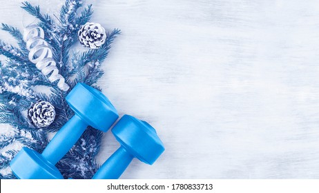 Dumbbells on the background of a spruce branch with Christmas decorations. The concept of sports lifestyle. Fitness and activity. Top view, flat lay, copy space. Copy space.