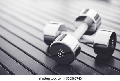 dumbbells on a wooden background in a gym, healthy lifestyle concept.Black and white tone.