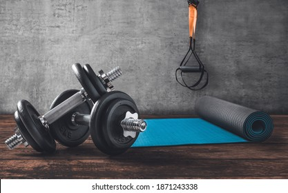 Dumbbells on wooden floor with yoga mat and TRX straps in the back.