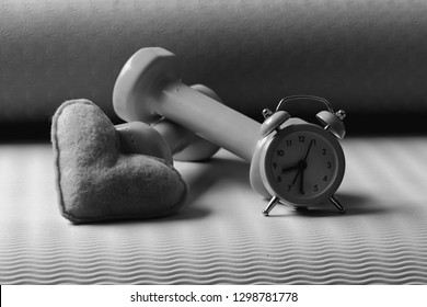 Dumbbells in pink color next to alarm clock and soft toy heart on green and purple background. Heart decoration near barbells on yoga mat. Love of sports and early training. Morning workout concept