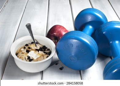 Dumbbells and red apple next to bowl with yogurt, muesli and honey on floor