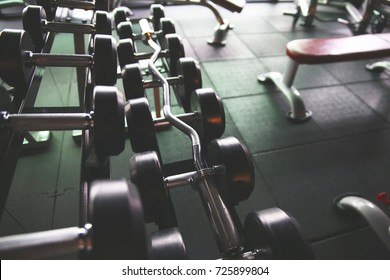 The Dumbbells row and barbell in the modern Gym background