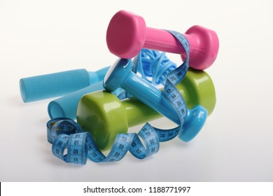 Dumbbells and skipping rope in cyan, pink and green color on light grey background. Fit shape and sport concept. Health regime and fitness symbols. Jump rope, barbells and tape tied around them