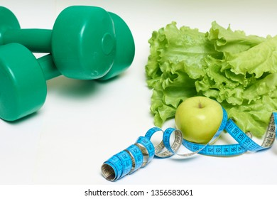 dumbbells surrounded with healthy fruits and vegetables