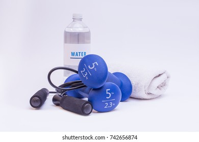 Dumbbells with towel, rope and water on isolated white background.