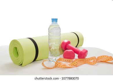 Dumbbells,yoga mat, bottle of water and measuring tape for fitness and healthy lifestyle concept.
