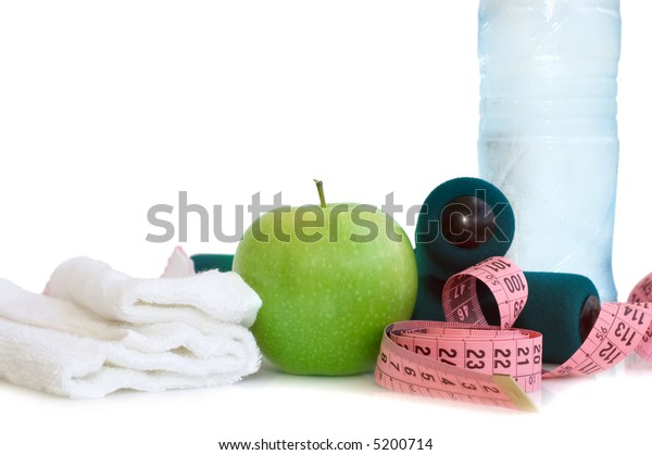 Dumbells, apple and measuring tape on a white background