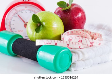 Dumbells with measuring tape and apples