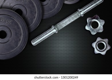 Dumbells and weights on a carbon background. Fastening screws and barbells.
