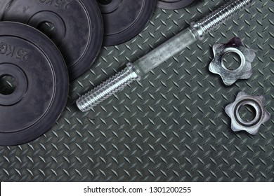 Dumbells and weights on the exercise mat. Fastening screws and barbells.