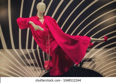 Dummy in a magnificent red dress in a show-window of shop. Fashion