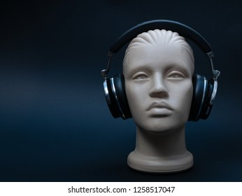 dummy mannequin head with over ear headphones on black background, low key image