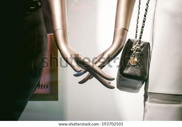 dummy on a shop window. Fingers of dummies with a handbag