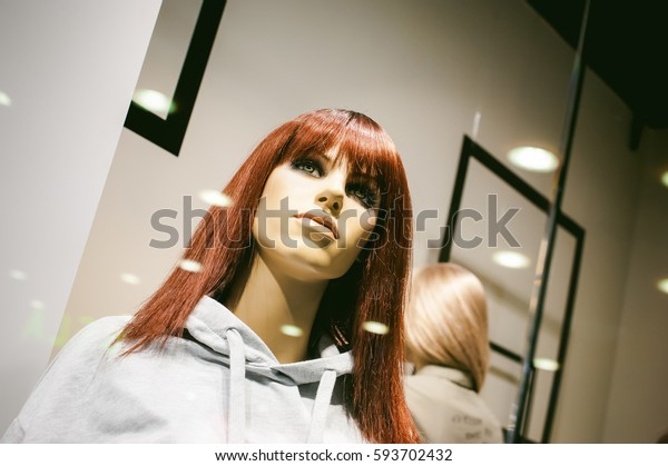 dummy on a shop window. Red-haired with a female human face