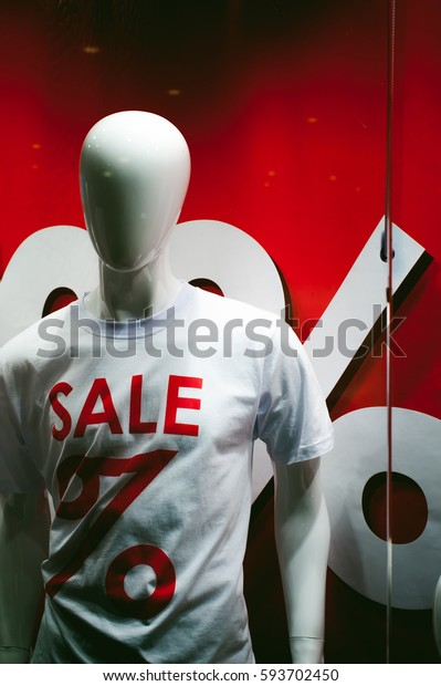 dummy on a shop window. White mannequin with an inscription on the chest t-shirts