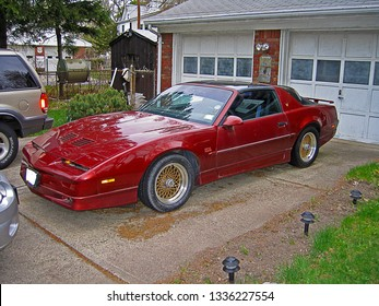 DUMONT, NEW JERSEY/USA - April 1, 2004: A Flame Red Metallic 1988 Pontiac Trans AM GTA parked in the driveway of a residential neighborhood.