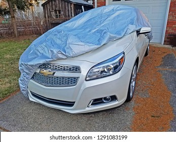 DUMONT, NEW JERSEY/USA - JANUARY 11, 2019: A 2013 Chevrolet Malibu LTZ parked partially under a car cover. The LTZ package comes with leather, front seat heaters,  LED taillights, and 19-inch wheels.