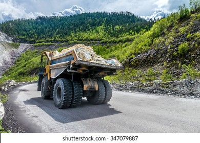 the dump truck carries the stones on the road