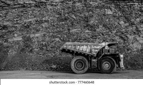 Dump truck in coal mine, black and white filter