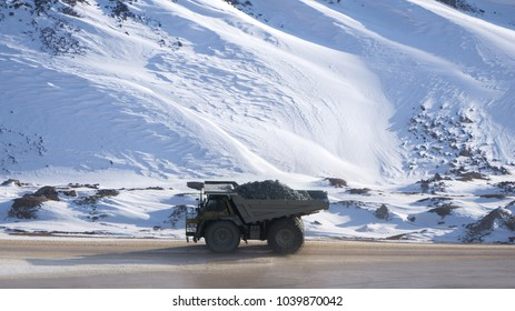 Dump truck loaded with ore driving through a snow covered open pit mine