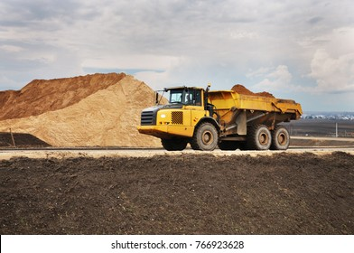 The dump truck is loaded with sand