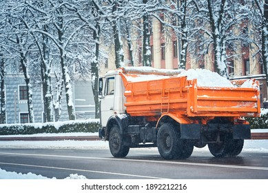 Dump truck loaded with snow driving through city street. Winter service vehicle - snow hauling and relocation, ice removal machine. Loded with snow driving trucks, cleaning streets and removing snow - Shutterstock ID 1892212216