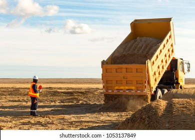 Dump truck is moving down sand on construction site. Leveling the ground. Signalman on construction site to assist dump truck driver to move down sand.