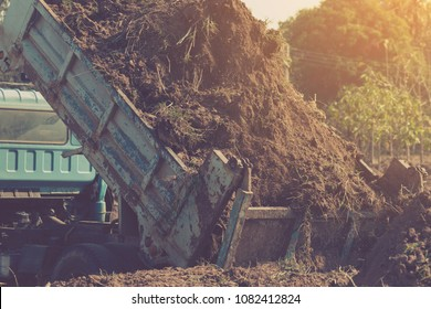 dump truck preparing ground for landscape improvement at property project;Dump truck dumping and tipping raw earth soil for construction site