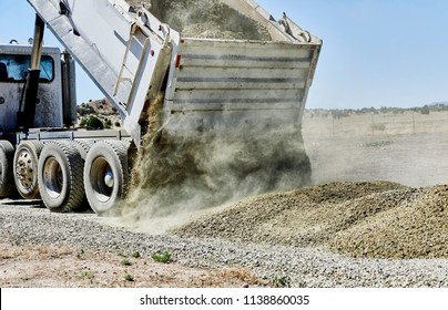 A dump truck spreading gravel on a dirt driveway