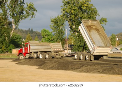 Dump truck and trailer laying down gravel base while working on a new tennis center, Stewart Park, Roseburg OR