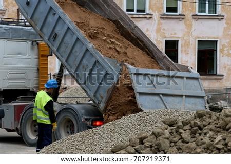 The Dump Truck Unloading Sand On Construction Site